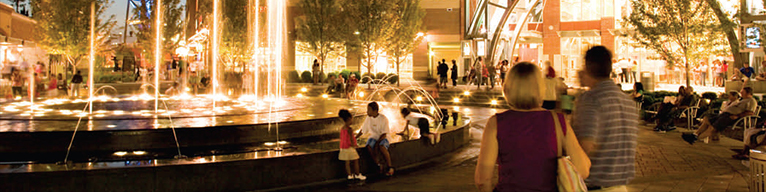 A brightly lit fountain surrounded by people and trees.