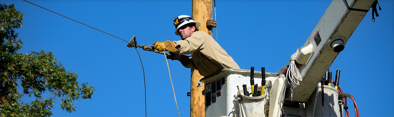 A man repairing a powerline from a lift.