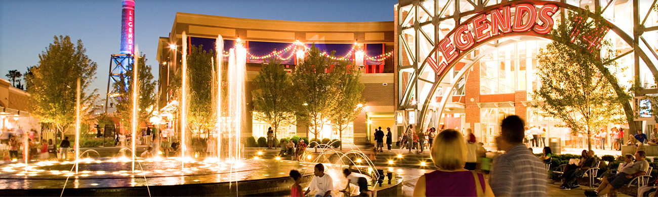 The Legends 14 movie theater, brightly lit. To its left is a fountain with lights shining under the streams of water.